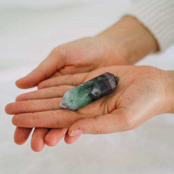 mano sosteniendo biterminado fluorita violeta